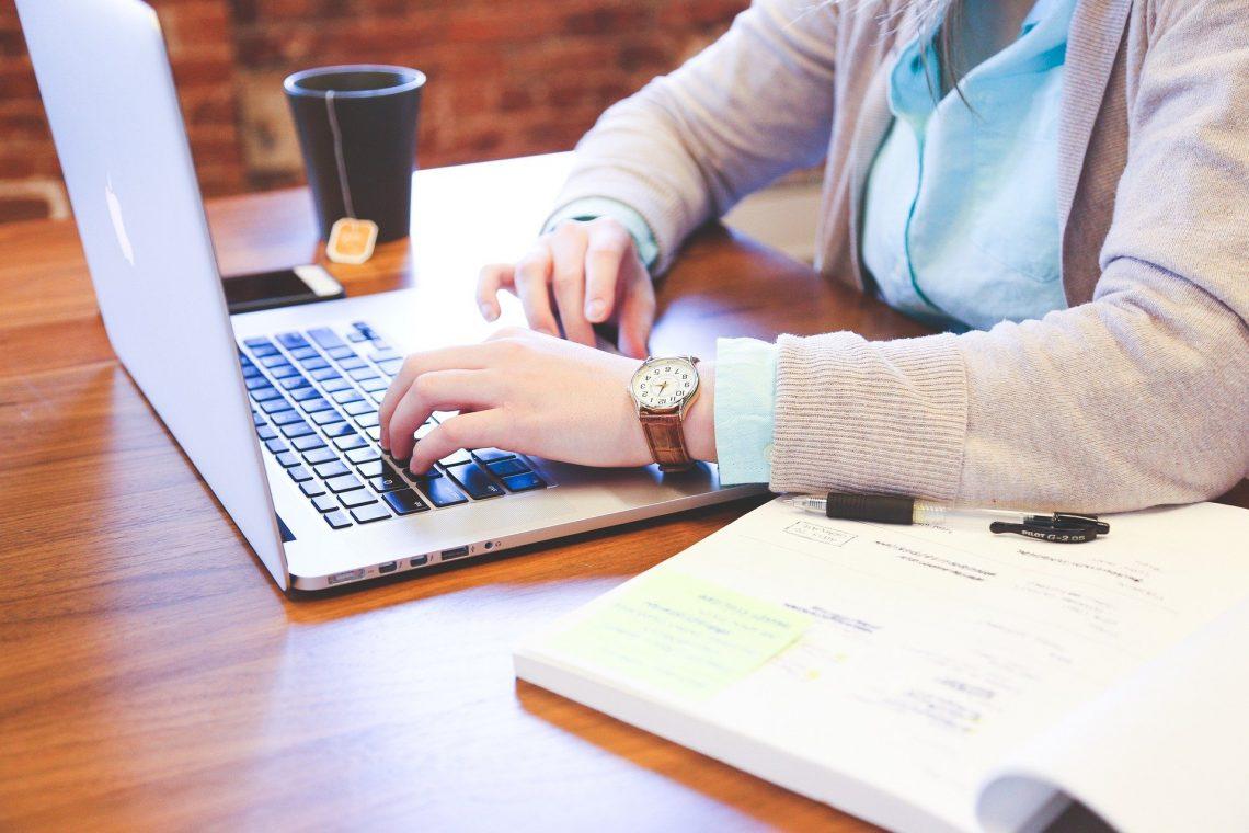 Osoba przy biurku z laptopem i kawą